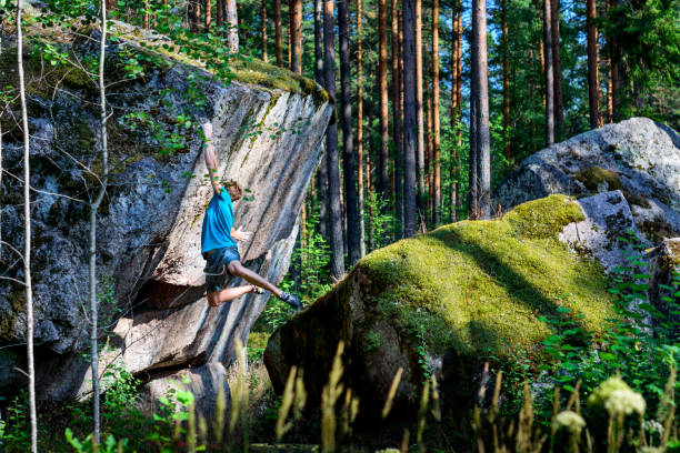 Male climber climbing overhanging rock. Boudering. Outdoor active lifestyle Male climber climbing overhanging rock. Boudering in northern forest. Outdoor active lifestyle. republic of karelia russia stock pictures, royalty-free photos & images