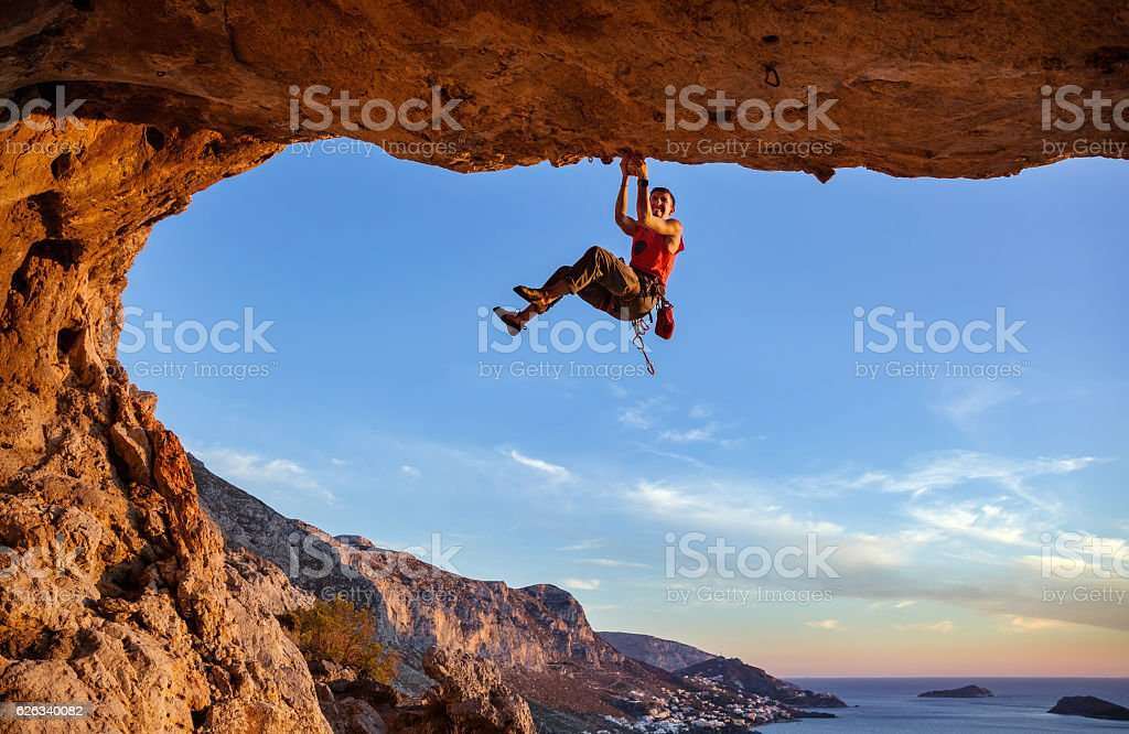 Male climber gripping on handhold while climbing in cave stock photo