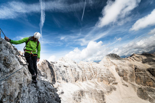 male climber on a steep and exposed Via Ferrata male climber on a steep and exposed Via Ferrata with a fantastic view in the South Tyrol in the Italian Dolomites steep stock pictures, royalty-free photos & images