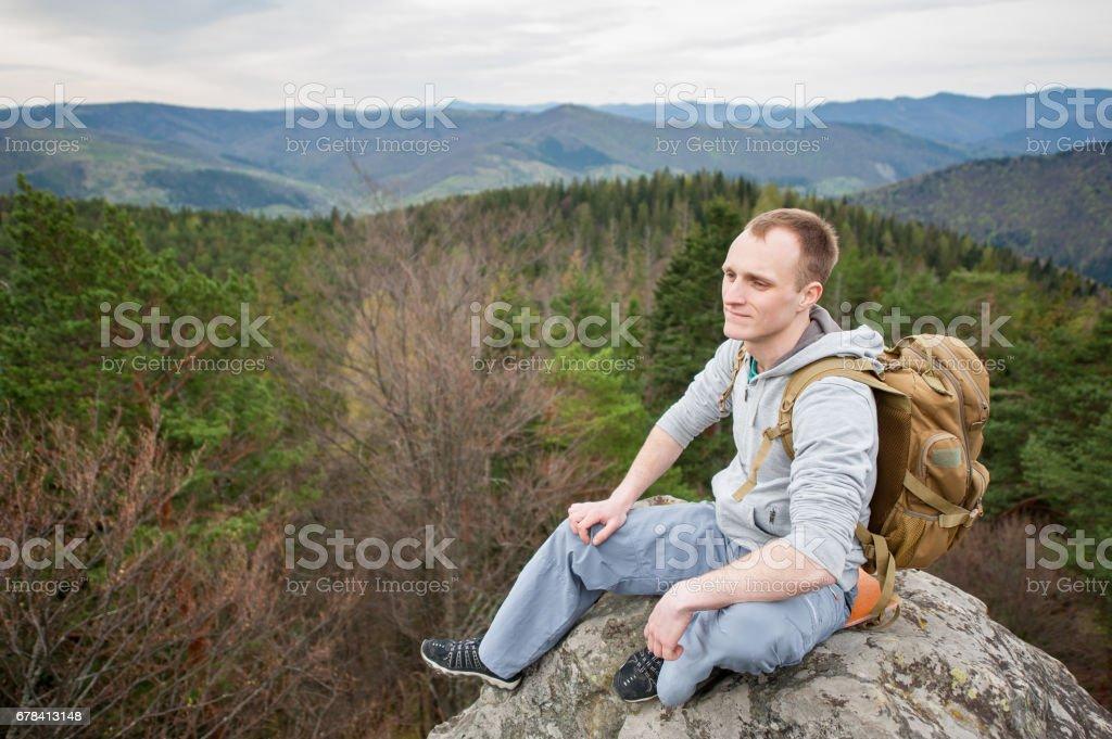 Alpinista masculina com mochila marrom no pico da pedra - foto de acervo
