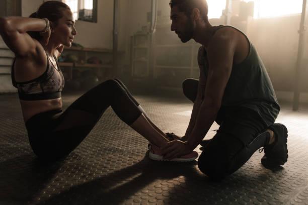男性コーチのジムで腹筋を行うことで女性を支援 - パーソナルトレーナー ストックフォトと画像