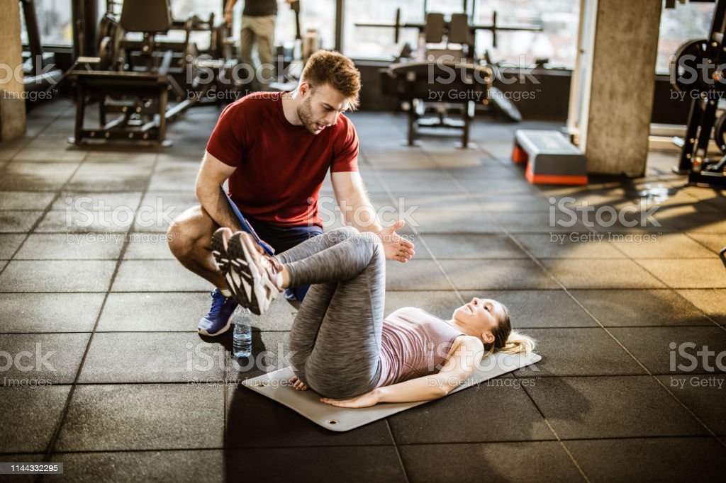 Young male coach assisting athletic woman in sports exercises during...