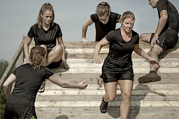 male coach helping women to cross wooden wall obstacle - obstacle run stockfoto's en -beelden