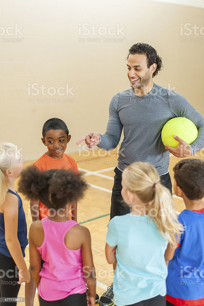 Male coach talking to team of young soccer players stock photo