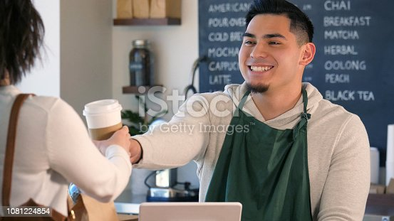 597640822istockphoto Male coffee barista smiles at customer as he hands her a drink 1081224854