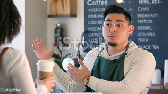 597640822istockphoto Male coffee shop employee gestures as he talks with a customer 1081224870