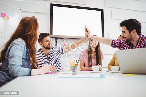 649403294 istock photo Male colleagues giving high-five in meeting at creative office 649454046