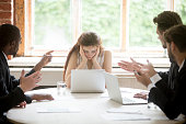 Male colleagues pointing fingers at upset female boss on meeting
