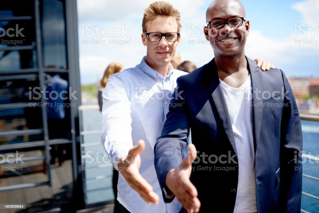 Male colleagues standing together with hands out stock photo