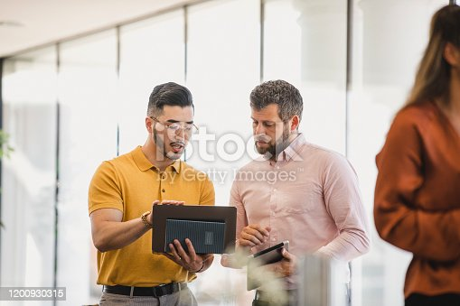Hipster man holding laptop and explaining to coworker, support, guidance, advice