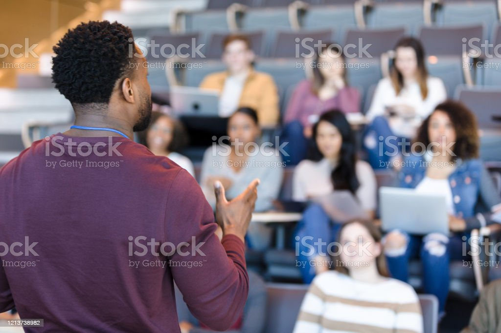 Male college professor gestures during lecture - Royalty-free Adult Stock Photo