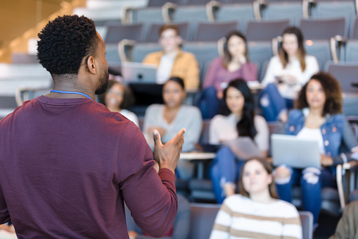 An African American male college professor gestures while giving a lecture to a group of college students.