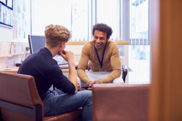 reunião de estudantes universitários masculinos com conselheiro do campus discutindo questões de saúde mental - professor - fotografias e filmes do acervo