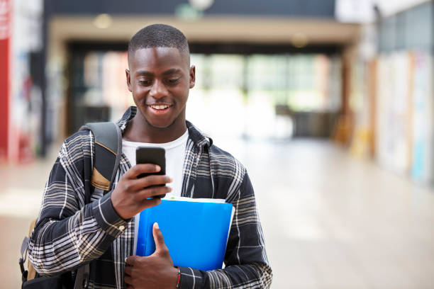 male college student reading text message on mobile phone - kids phones stock photos and pictures