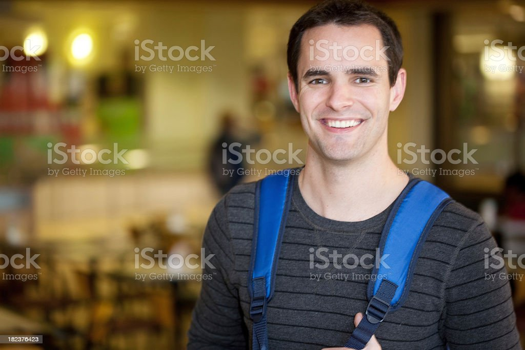 Male College Student Standing in the University Cafeteria royalty-free stock photo