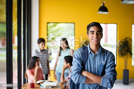 istock Male college student standing with students in background 836568130