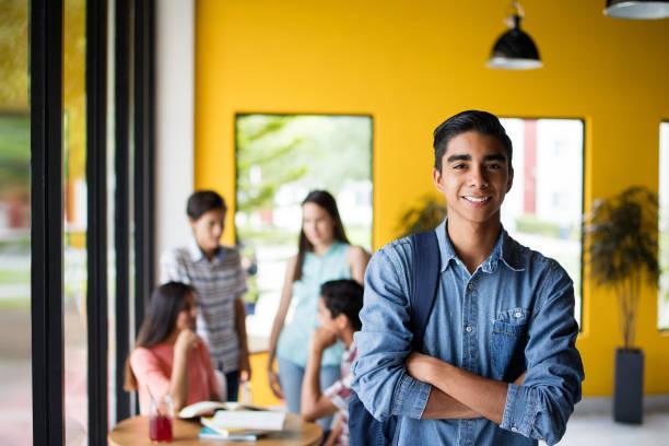 männliche college-student mit studenten im hintergrund stehend - mexikanische möbel stock-fotos und bilder