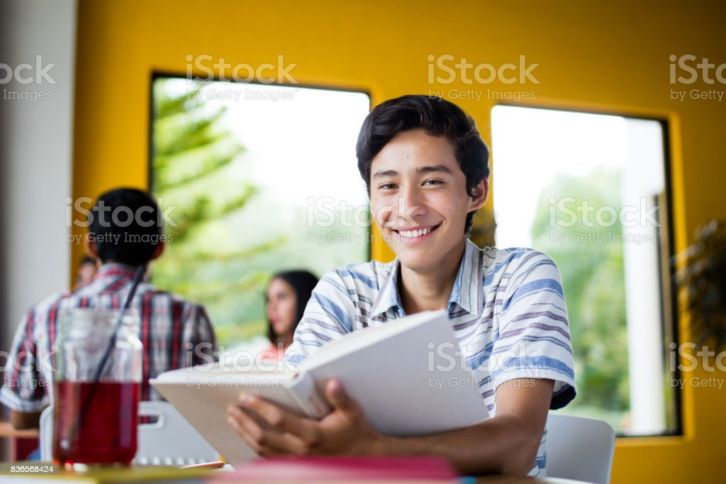 Male college student with book smiling at camera stock photo