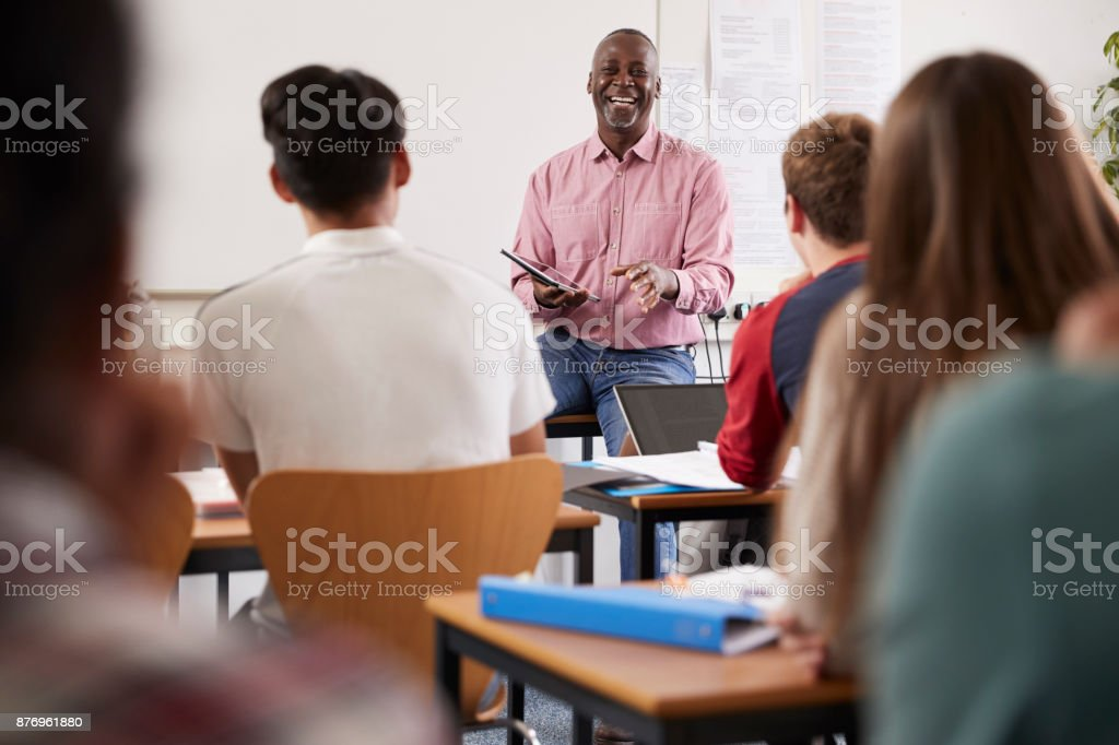 Male College Tutor With Digital Tablet Teaching Class stock photo