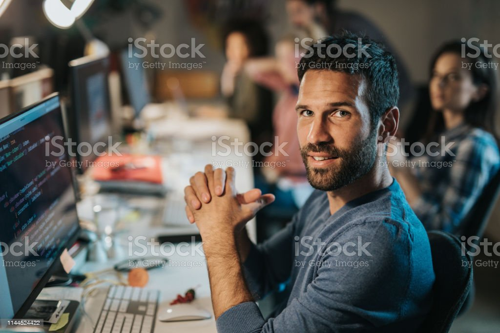 Young programmer coding data while working on desktop PC in the...
