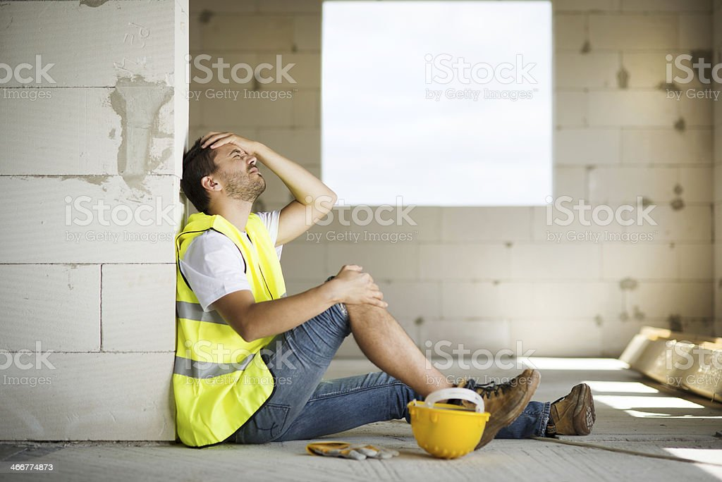 Male construction worker agonizes over accident at worksite stock photo