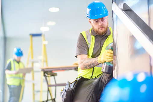 a male carpenter is installing handrails  in a modern office refurbishment. IN the background a female co-worker can be seen holding plans . They are wearing safety workwear.