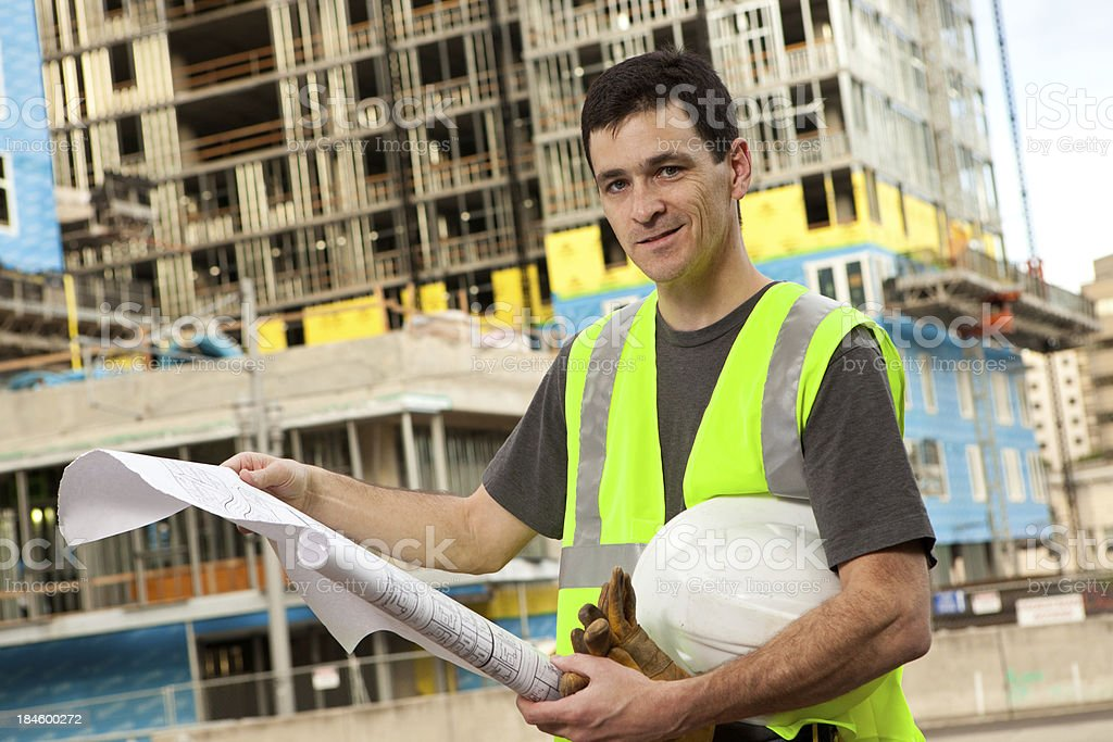 Male Construction Worker Holding Building Plans royalty-free stock photo