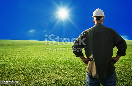 Close up rear view of male construction worker on green grass landscape over sunny blue sky