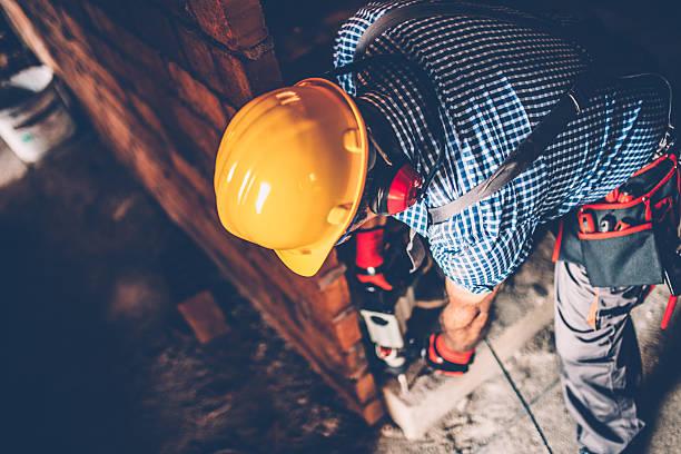 male construction worker with a drill - legere arbeitskleidung stock-fotos und bilder