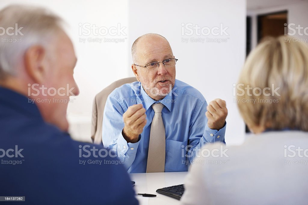 Male consultant motivating the senior couple royalty-free stock photo