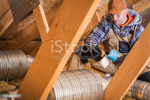895571294 istock photo Male Contractor Binding Ventilation Pipes With Duct Tape. 1254821321
