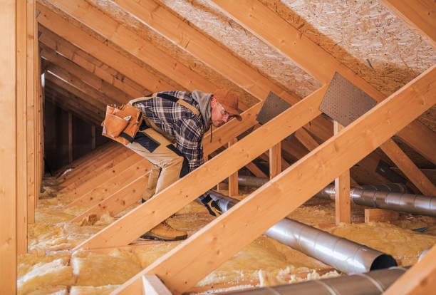 Male Contractor Installs Metal Pipe System In Attic. stock photo