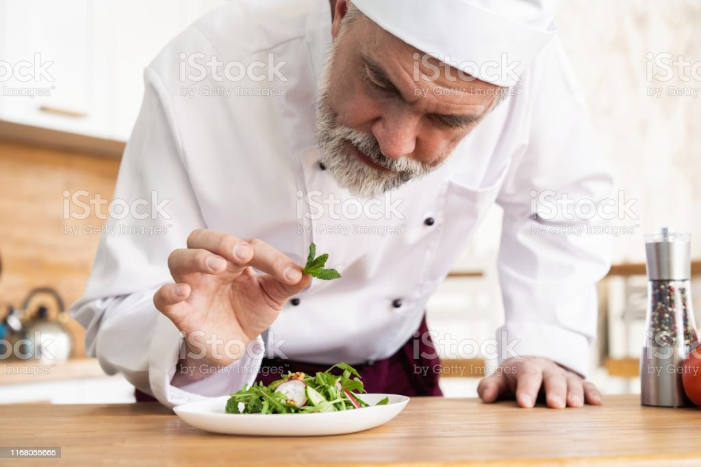 Male Cook Chef Decorating Garnishing Prepared Salad Dish On The Plate In Restaurant Commercial Kitchen Stock Photo Download Image Now Istock
