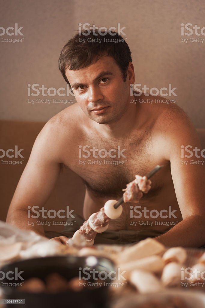 Male cook meat on a spit stock photo