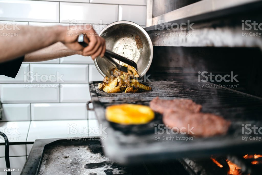Male cook prepares grilled potato - Royalty-free Backgrounds Stock Photo