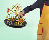 male cook roasting flying vegetables and shimps