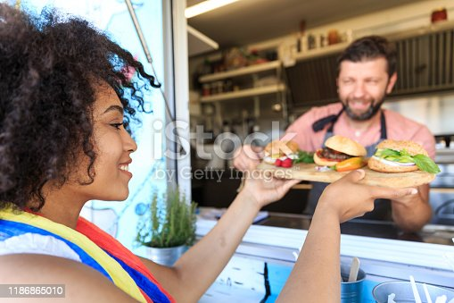 istock Male cook selling burgers and sandwiches in food truck 1186865010