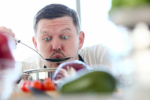 männlicher koch probiert heiße suppe aus pfanne - pfannen test stock-fotos und bilder