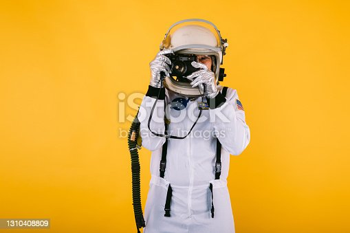 Male cosmonaut in space suit and helmet, taking a picture with a retro camera, on yellow background.