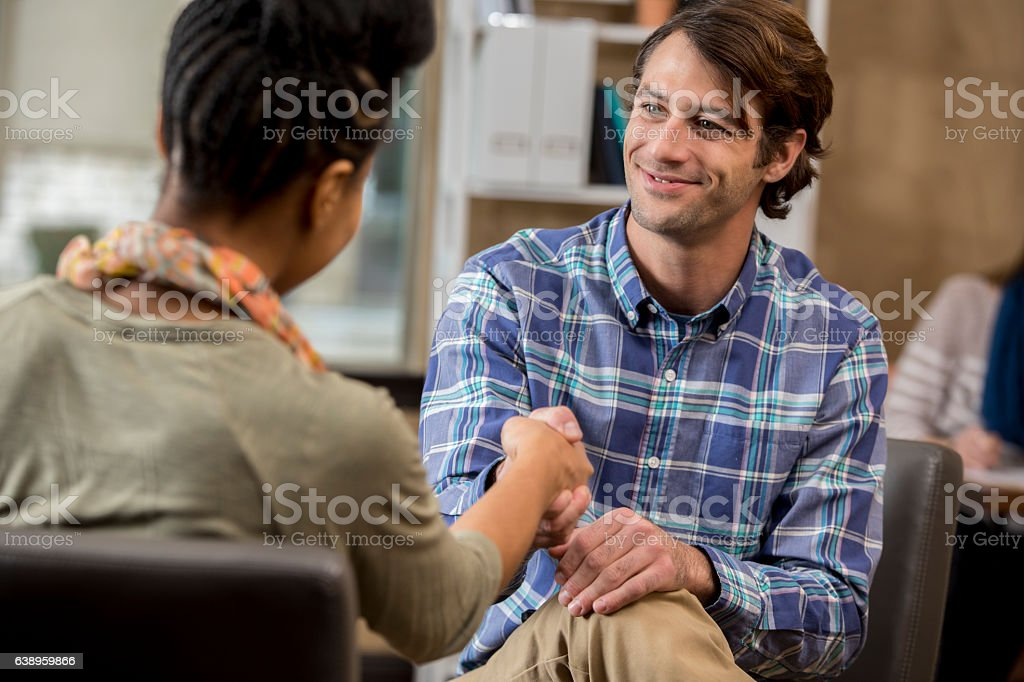 Male counselor greets new patient stock photo