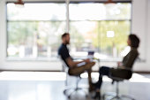 Defocused view of a male therapist talking with a female client.