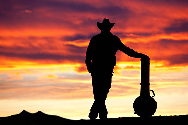 Male Country Musician Silhouette A silhouette of a country musician standing with a banjo. Cowboy. Dramatic sunset. Relaxed. Unrecognizable male roots music singer songwriter with banjo and acoustic instrument standing against an amazing sunset. Wearing cowboy hat. Themes include country music, roots music, poet, guitar player, guitar, banjo, stringed instrument, bluegrass, country music, outside, festival, music festival, arts entertainment, and guitars. Male singer is unrecognizable.  country and western music stock pictures, royalty-free photos & images