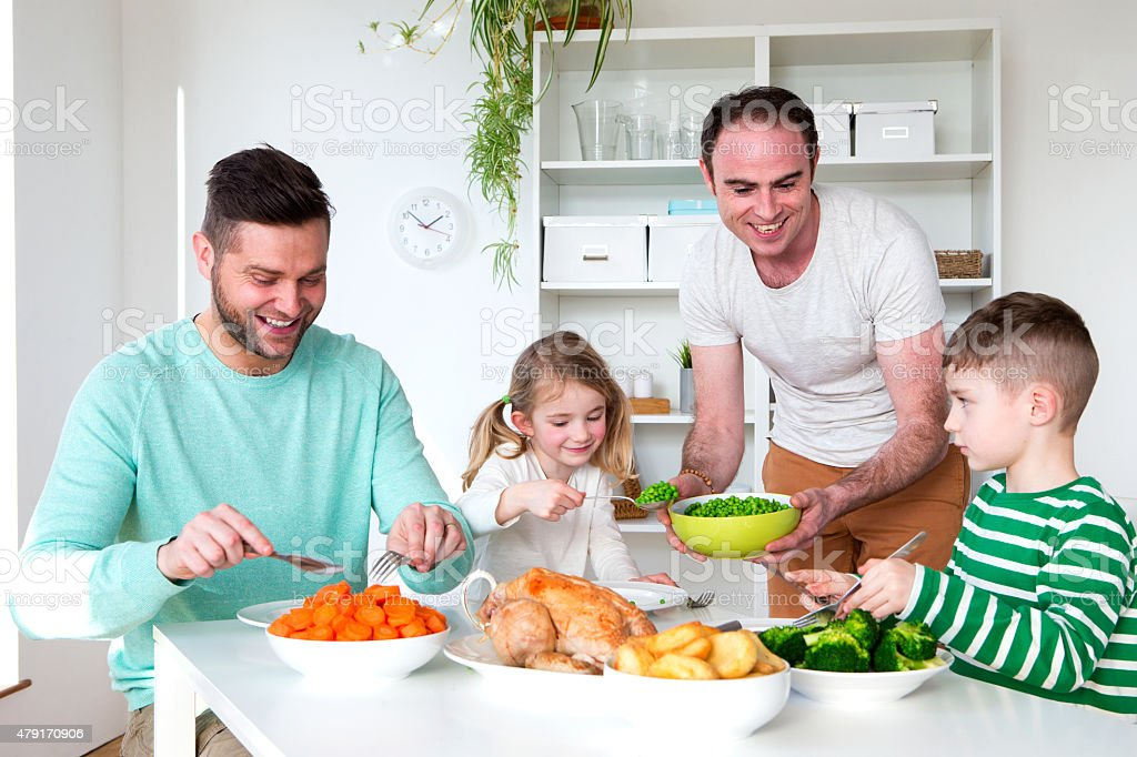 Male couple having dinner with their son and daughter stock photo