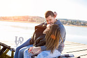 male couple, kissing, while sitting on wooden pier at riverbank