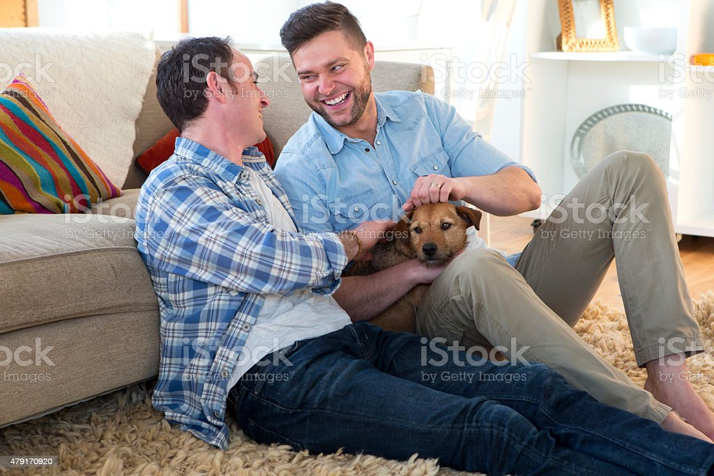 Male couple sitting with their pet dog stock photo
