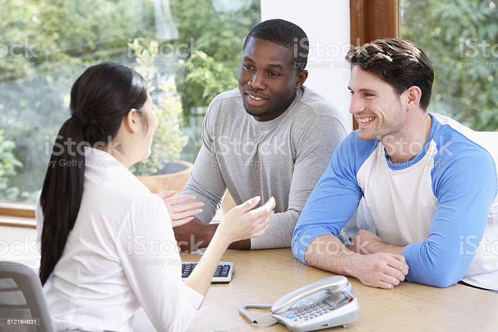 Male Couple Talking With Financial Advisor Male Couple Talking With Financial Advisor In Office 20-29 Years Stock Photo