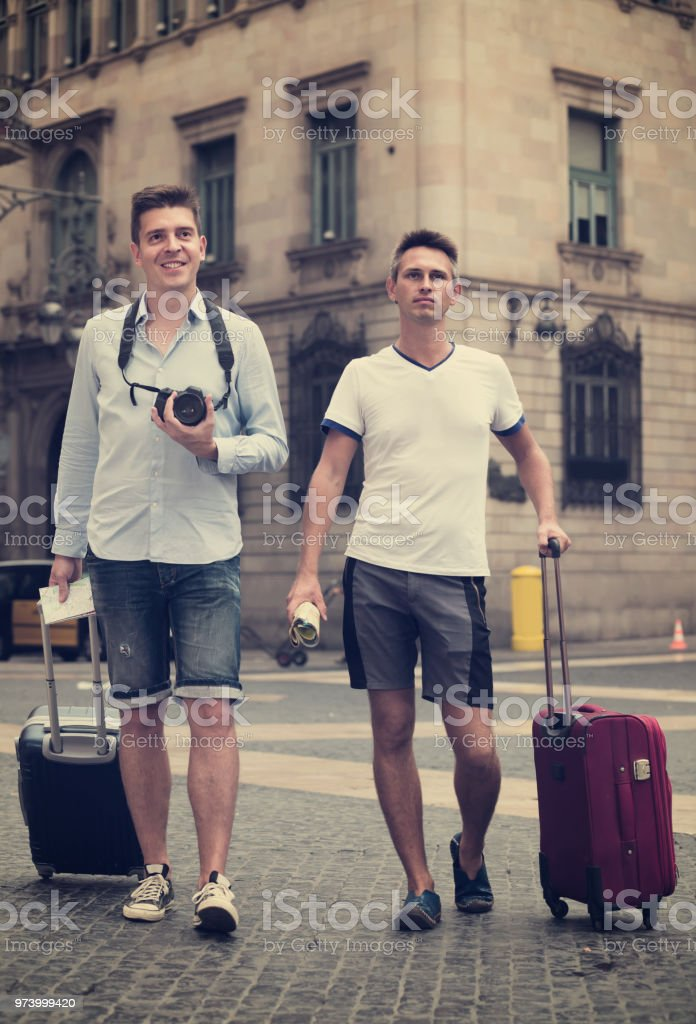 Male couples with travel bags walking the city stock photo