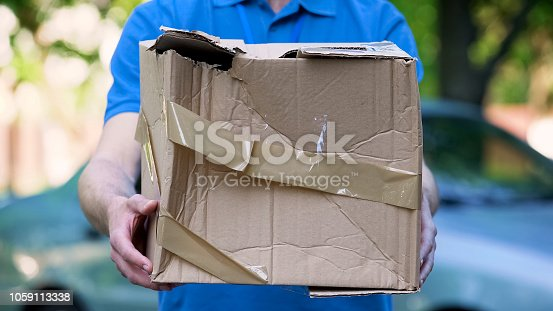 Male courier showing damaged box, cheap parcel delivery, poor shipment quality