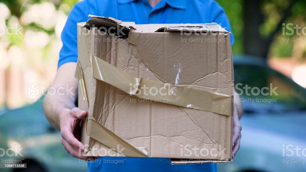 Männliche Kurier zeigt beschädigt Box, billige Paketzustellung, schlechte Sendung Qualität – Foto
