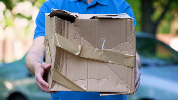 männliche kurier zeigt beschädigt box, billige paketzustellung, schlechte sendung qualität - was bringt unglück stock-fotos und bilder